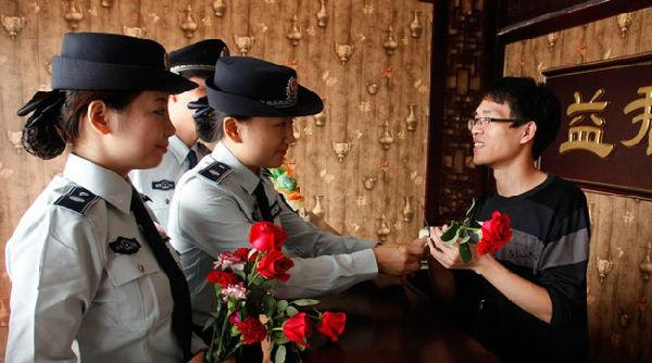 武汉,美女执法队员手拿鲜花,在执法中送给配合执法的商户,并送上节日的祝福。